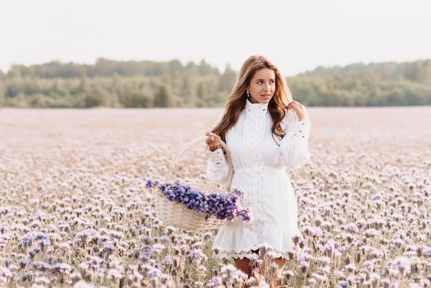 Fille sur le terrain avec un bouquet de fleurs dans un panier dans la nature en été