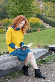 Fille de tête de lecture assise dans un parc