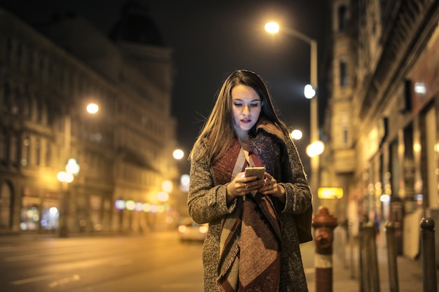 Fille textos dans la rue la nuit