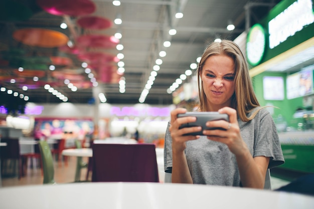 Fille de textos sur le téléphone intelligent dans un restaurant