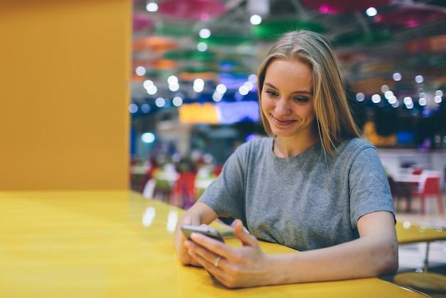 Fille de textos sur le téléphone intelligent dans une terrasse de restaurant avec un mur flou.