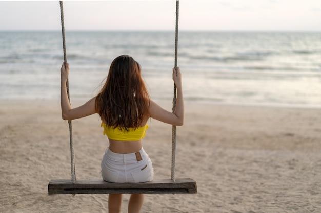 Une fille thaïlandaise asiatique en robe jaune et blanche était assise sur une plaque de balançoire en bois et regardait la ligne horizontale de la mer à l'infini à l'heure dorée du crépuscule.