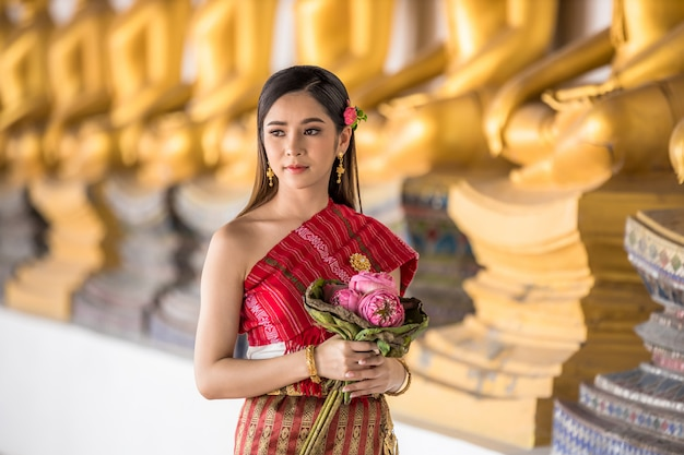 Fille thaïlandaise en costume thaïlandais traditionnel tenant un lotus dans un temple thaïlandais, culture d'identité de la thaïlande.
