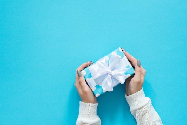 Fille tient une boîte-cadeau, une boîte-cadeau à pois avec un ruban blanc et un arc sur un mur bleu