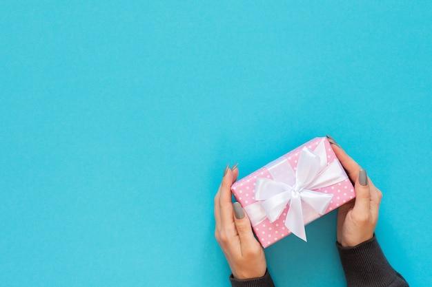 Fille tient une boîte-cadeau, une boîte-cadeau rose à pois avec un ruban blanc et un arc sur un bleu