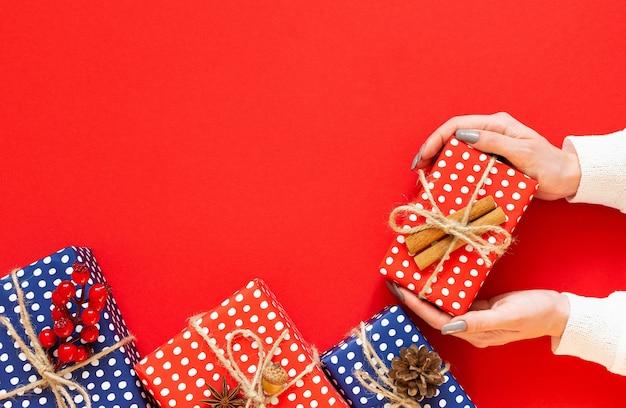 Une fille tient une boîte-cadeau, des coffrets cadeaux rouges et bleus à pois avec un cône d'arbre de noël et des brindilles d'aubépine avec du gland et de la cannelle sur fond vert, mise à plat, vue de dessus