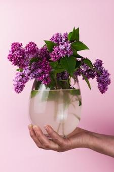 Fille tient un bouquet de lilas dans un vase sur un mur rose pastel