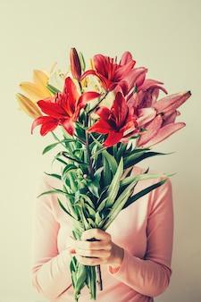 Fille tient un bouquet de lis dans ses mains, cache son visage en fleurs