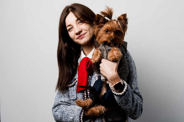 Fille tient un chien brun isolé. jeune femme séduisante avec chien yorkshire terrier sourit. gros plan photo. s'occuper d'un animal. les gens et les animaux.