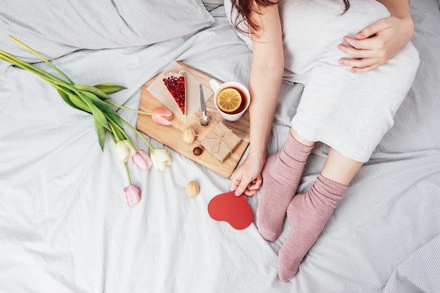 La fille tient un coeur rouge. félicitations pour la saint-valentin le 14 février. petit-déjeuner au lit et cadeau.