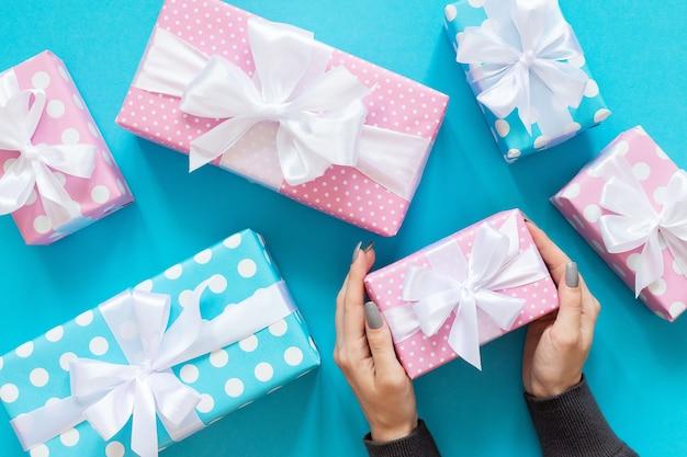 Une fille tient un coffret cadeau, des coffrets cadeaux roses et bleus à pois avec un ruban blanc et un arc sur fond bleu, à plat, vue de dessus, anniversaire ou saint valentin