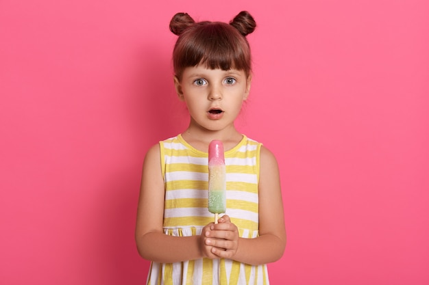 Fille tient la crème glacée avec la bouche largement ouverte, appréciant le dessert isolé sur rose