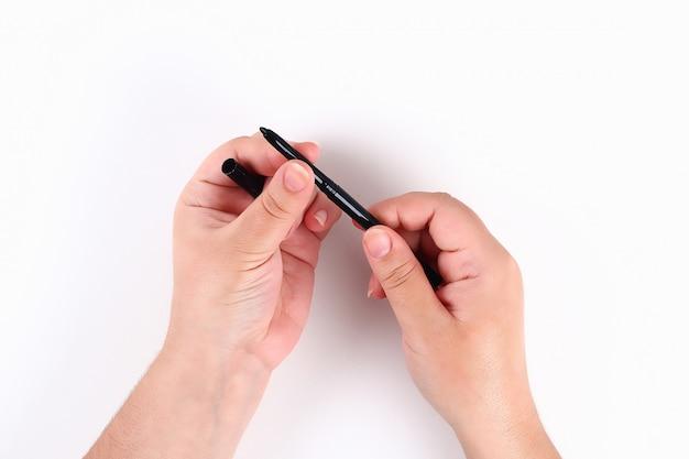La fille tient dans la main un eye-liner noir sur blanc. vue de dessus.