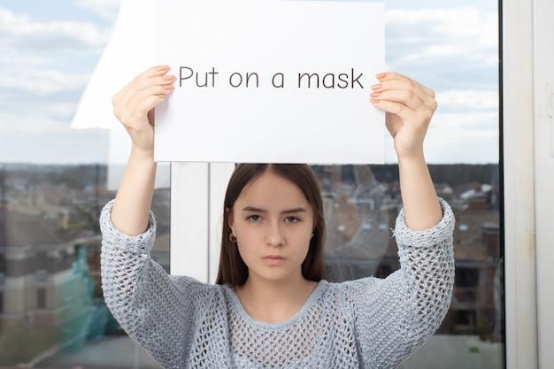 La fille tient dans les mains une feuille avec l'inscription mise sur un masque