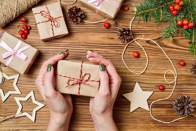 La fille tient dans sa main une boîte-cadeau sur le fond des accessoires de noël