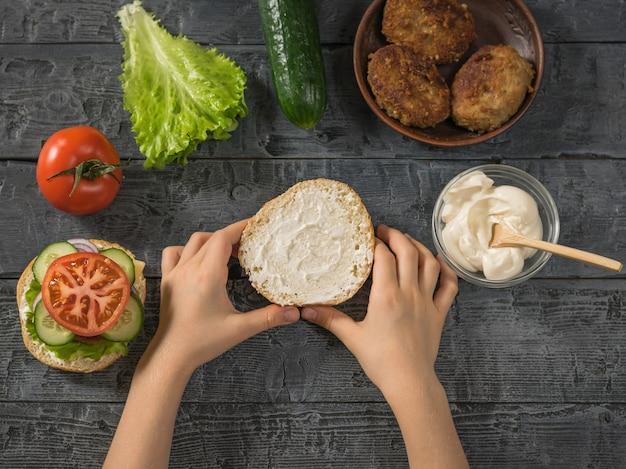 La fille tient dans ses mains l'autre moitié du pain à hamburger.