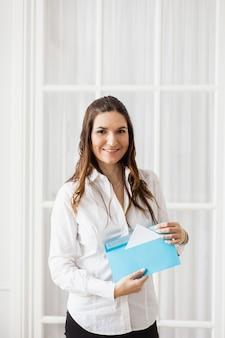 Fille tient une enveloppe, enveloppe avec lettre ou course, tâche