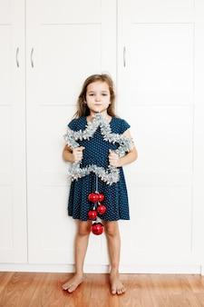 Une fille tient une étoile dans ses mains pour décorer la maison pour le nouvel an et noël, l'enfant se prépare pour les vacances, aide les parents, attend des cadeaux