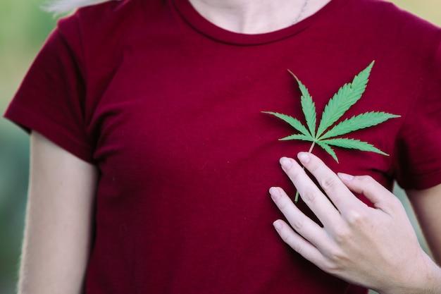Une fille tient une feuille de marijuana sur sa poitrine.