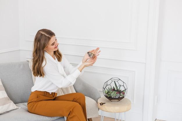 Une fille tient un florariumov, forme de verre avec des plantes succulentes, des pierres et du sable, décoré avec des rubans de noël. cadeaux de noël pour la maison et le bureau.