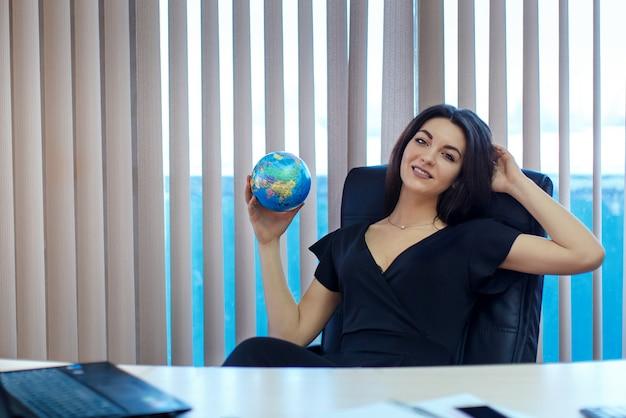 Une fille tient un globe dans ses mains