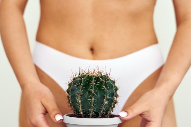 Fille tient un gros cactus dans l'aine ou le bikini.