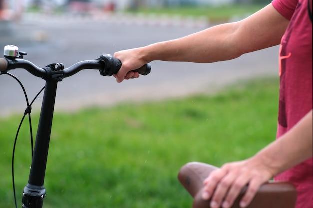 La fille tient le guidon du vélo dans un style magnifique.