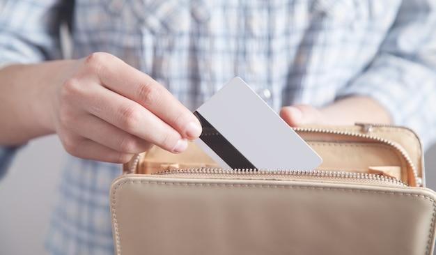 La fille tient et insère la carte de crédit dans son portefeuille.
