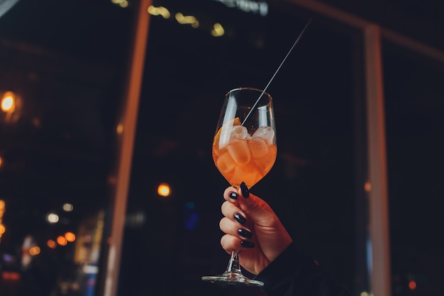 Une fille tient à la main un verre transparent de cocktail rouge, des glaçons flottent dans le verre.