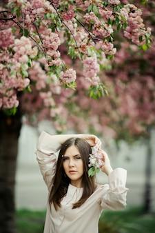 Fille tient les mains derrière la tête avec une branche de sakura