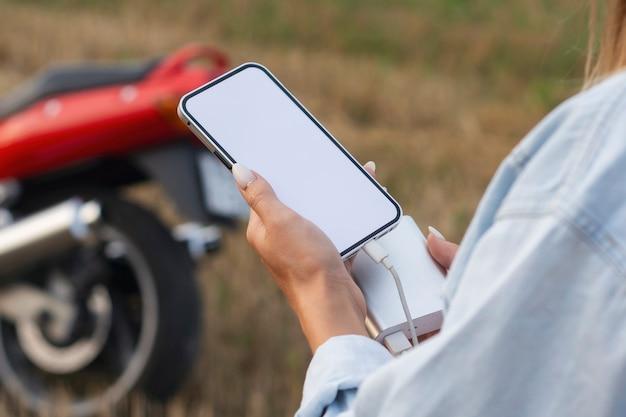 Une fille tient une maquette d'un smartphone avec un écran blanc dans les mains. power bank charge le téléphone dans le contexte de la nature et d'une moto.