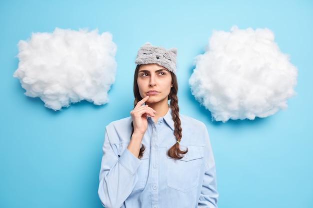 Une fille tient le menton des rêves éveillés à propos de quelque chose a deux nattes porte un masque de sommeil sur le front fait des suppositions avant d'aller dormir isolé sur bleu