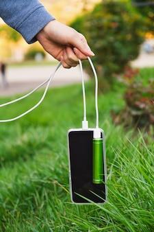 Fille tient par câble un smartphone et une banque d'alimentation externe pendant la charge