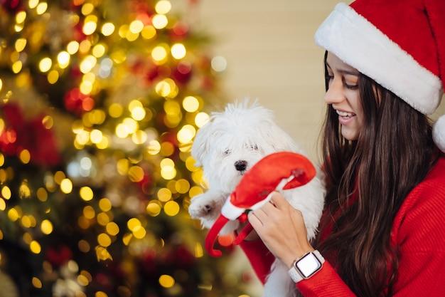 Une fille tient un petit chien sur ses mains au nouvel an nouvel an avec un ami