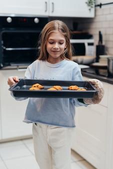 La fille tient un plateau avec des biscuits fraîchement préparés.