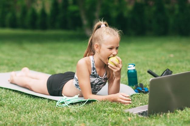 Une fille tient une pomme dans sa main après avoir suivi une formation en plein air en ligne
