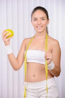 La fille tient une pomme dans ses mains et un centimètre.