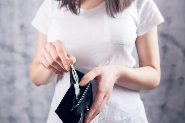 La fille tient le portefeuille dans ses mains et prend de l'argent