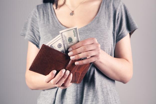 Fille tient le portefeuille dans ses mains et prend de l'argent