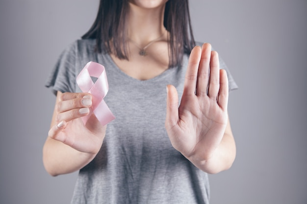 Une fille tient un ruban avec un signe de cancer dans sa main et montre un panneau d'arrêt avec l'autre main