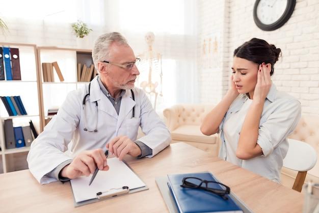 La fille tient sa tête et dit au médecin ce qui lui fait mal.