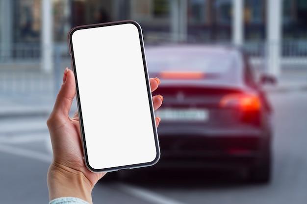La fille tient un smartphone dans ses mains. maquette de téléphone avec écran blanc sur le fond de la voiture.