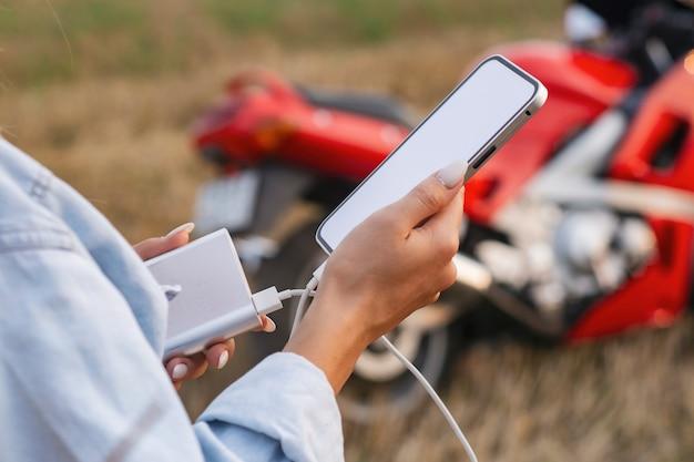 La fille tient un smartphone dans ses mains. power bank charge le téléphone dans le contexte d'une moto et de la nature.
