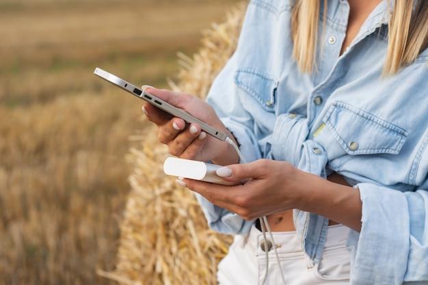 La fille tient un smartphone dans ses mains. power bank charge le téléphone dans le contexte de la nature.