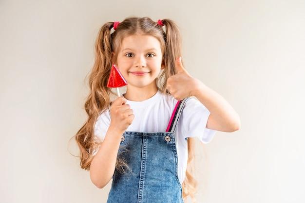 Une fille tient une sucette pastèque rouge