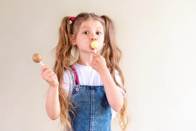 Une fille tient une sucette.