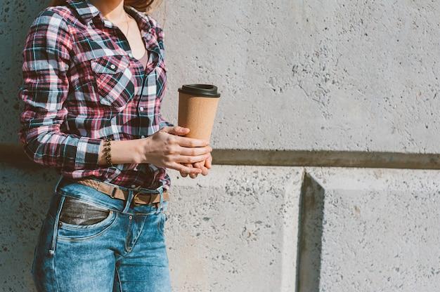 La fille tient une tasse thermo avec du café à la main.