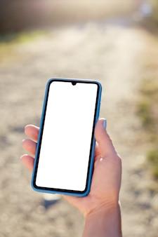 Fille tient un téléphone mobile en vacances dans la nature. maquette
