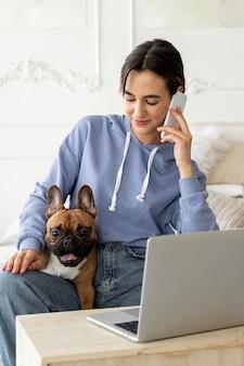 Fille de tir moyen avec chien parlant au téléphone