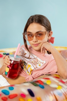 Fille de tir moyen avec lunettes de soleil et boisson